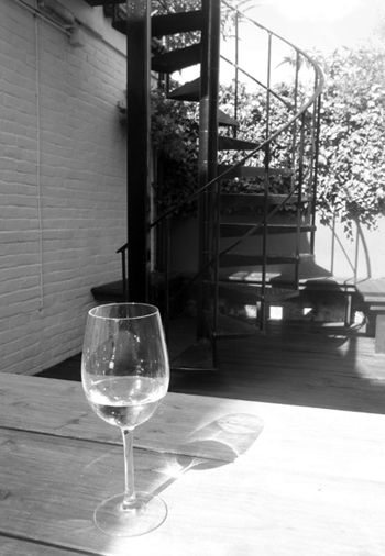 black-and-white photo of a partly filled wine glass on an outside table