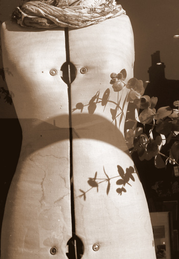 black-and-white photo of a dressmaker's dummy in a shop window